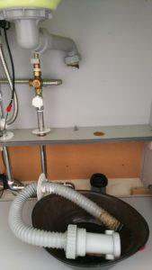 キッチン下の排水パイプの写真