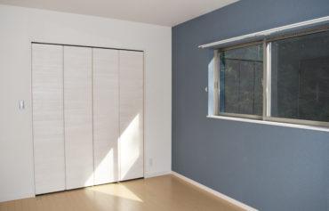 ワンポイントのブルーカラーの壁がアクセントの洋室