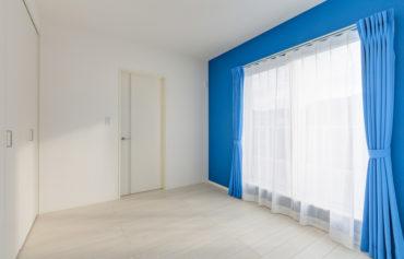 ブルーカラーがアクセントの明るい洋室
