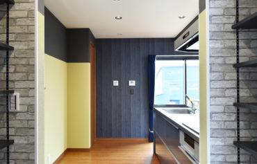 レンガ調デザインのパントリーに隣接したキッチン