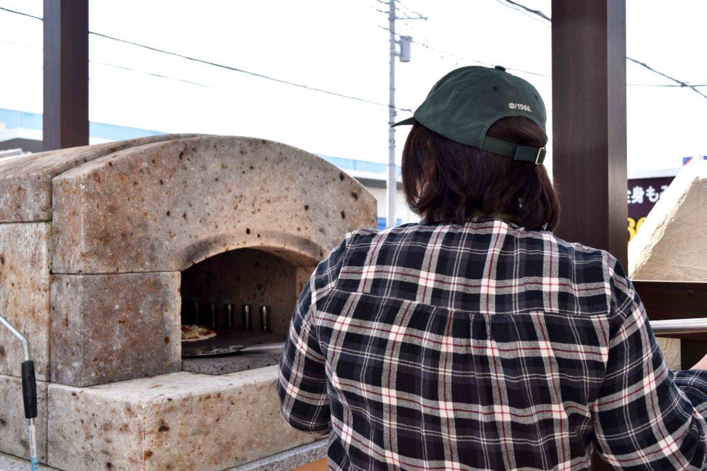 2020年3月21日に石窯でピザを焼く事務員の籾井さん