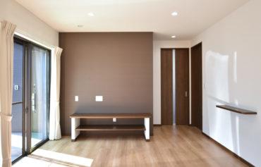 落ち着いた色合いのリビングの背面壁と、こだわりのテレビ台。