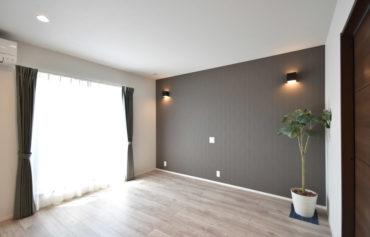 バルコニーと隣接する日当たりの良い主寝室。落ち着いた色合いのアクセントクロスとウォールライトが癒しの空間を演出。