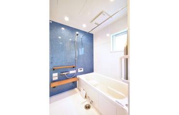 ブルーのアクセントパネルがお洒落な明るいバスルーム。