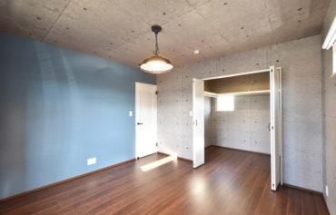 コンクリート調のクロスに、ブルーのアクセントクロスが映える主寝室。