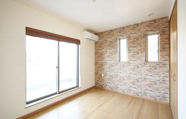 レンガ調のアクセントクロスがお洒落な洋室。バルコニーに隣接する明るい空間です。