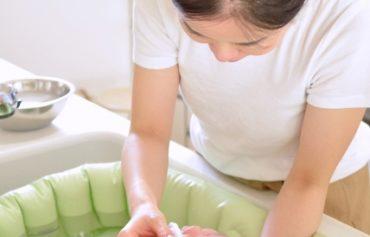 キッチンのシンクで赤ちゃんの沐浴をしている写真
