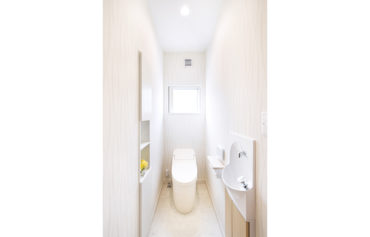 白で統一したお洒落で明るいトイレ。装飾や収納に活用できるニッチを造作。